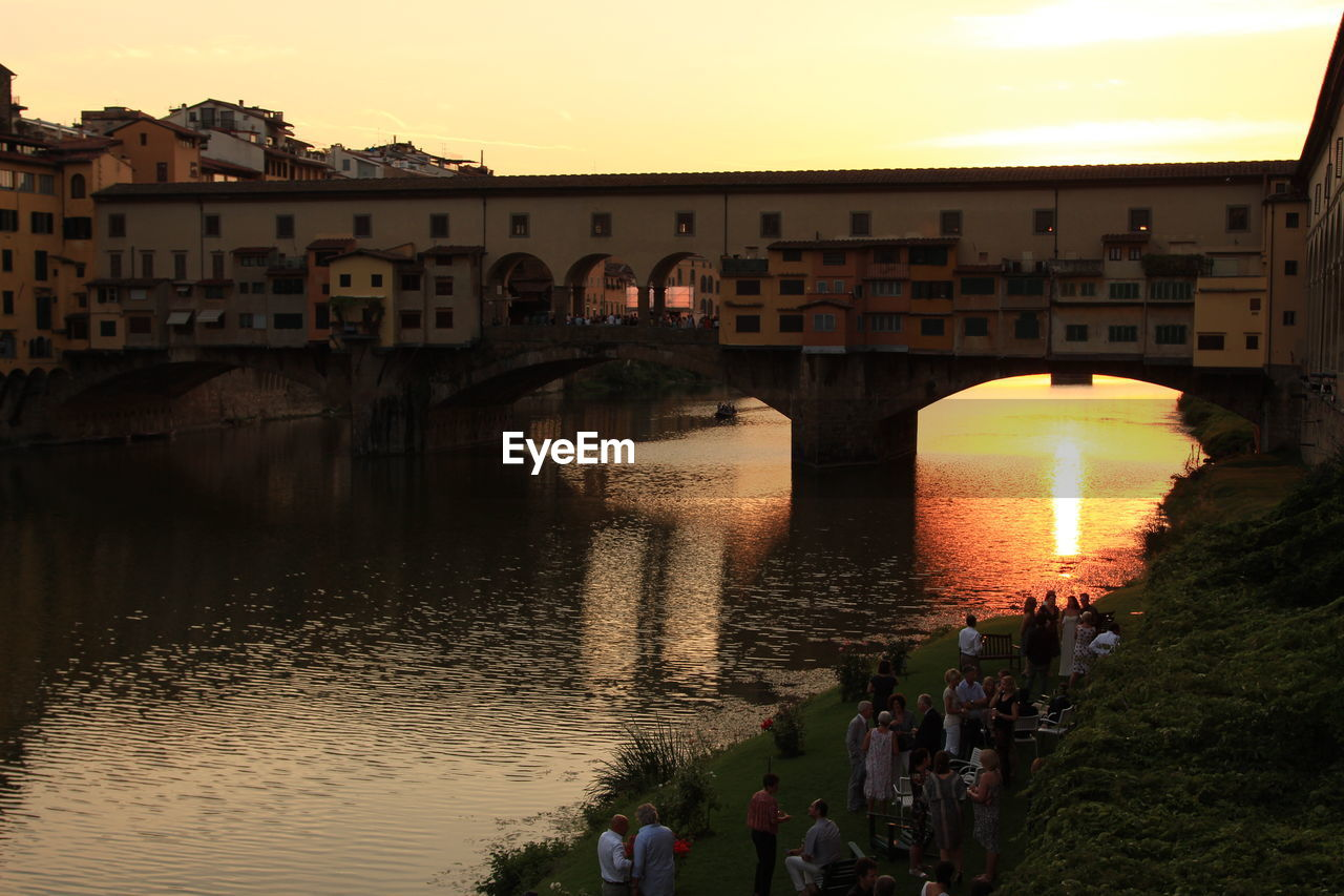 High Angle View Of People By Arno River Against Ponte Vecchio