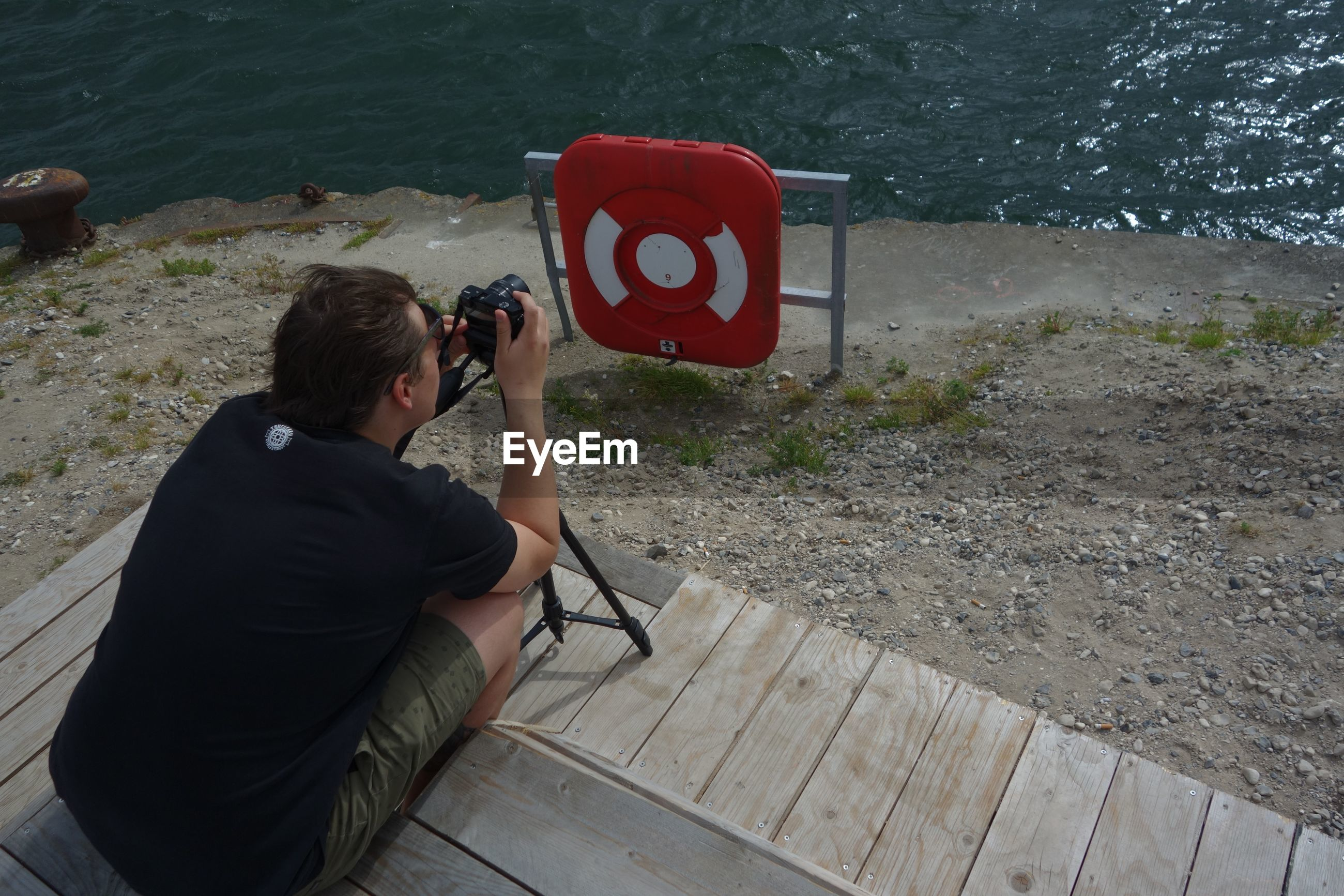 MAN PHOTOGRAPHING WHILE SITTING ON RIVER