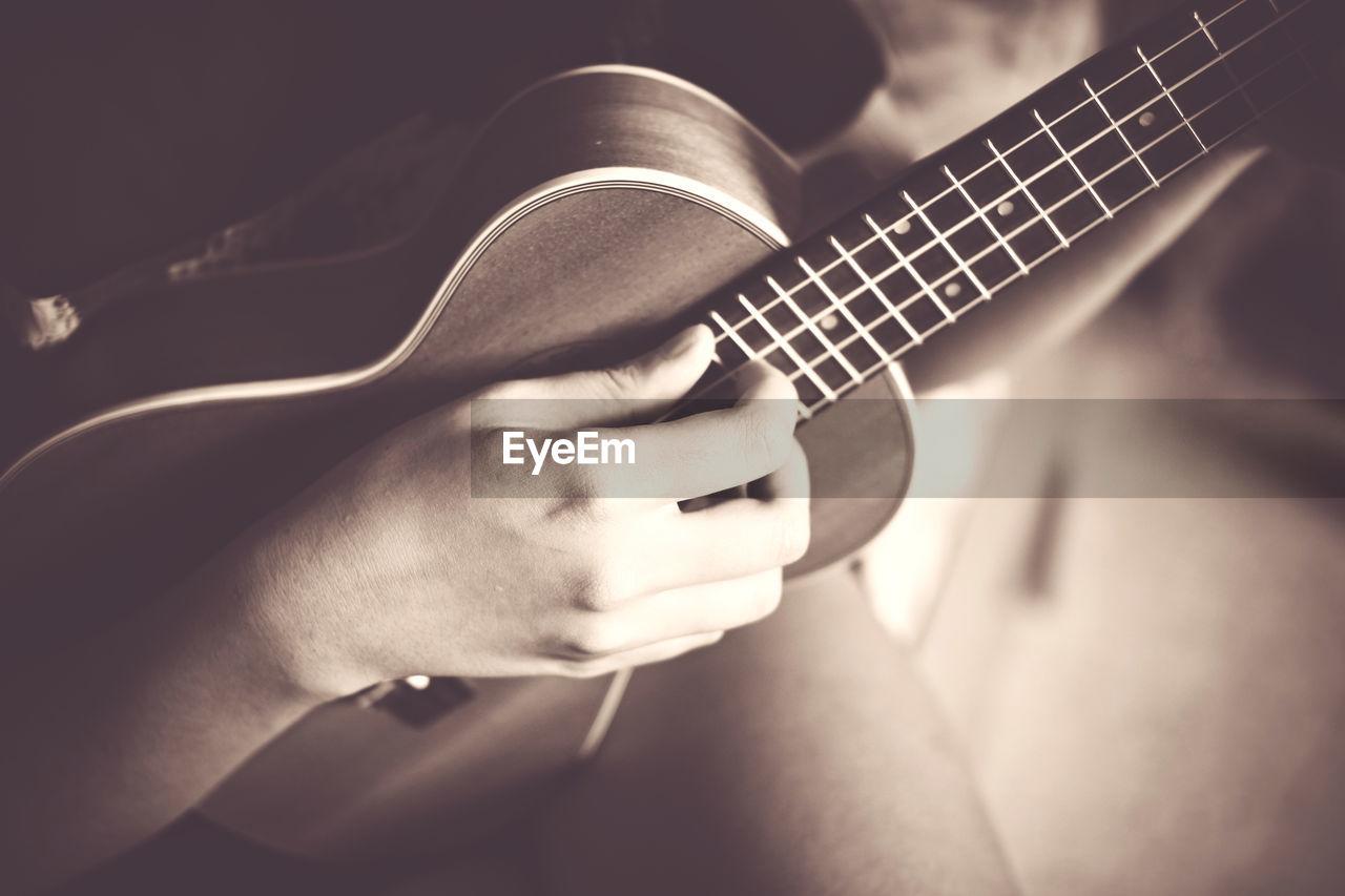 Close-Up Of Woman Playing Guitar