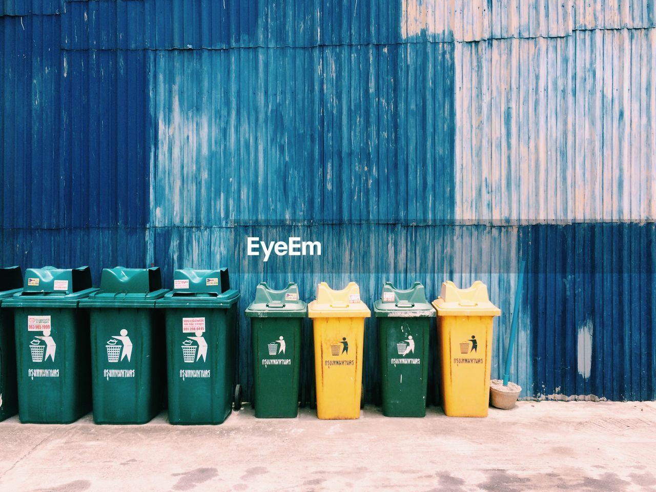 garbage bin, in a row, no people, recycling, recycling bin, blue, wall - building feature, day, architecture, side by side, nature, environmental conservation, multi colored, environment, built structure, environmental issues, garbage can, sunlight, green color, plastic