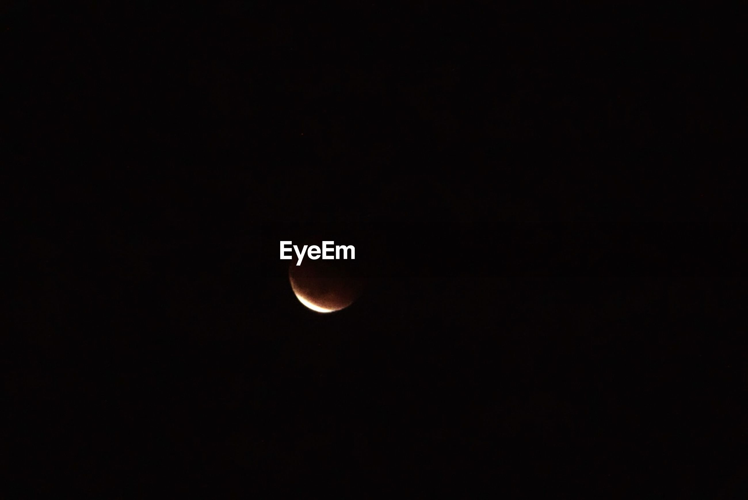 Low angle view of lunar eclipse against clear sky at night