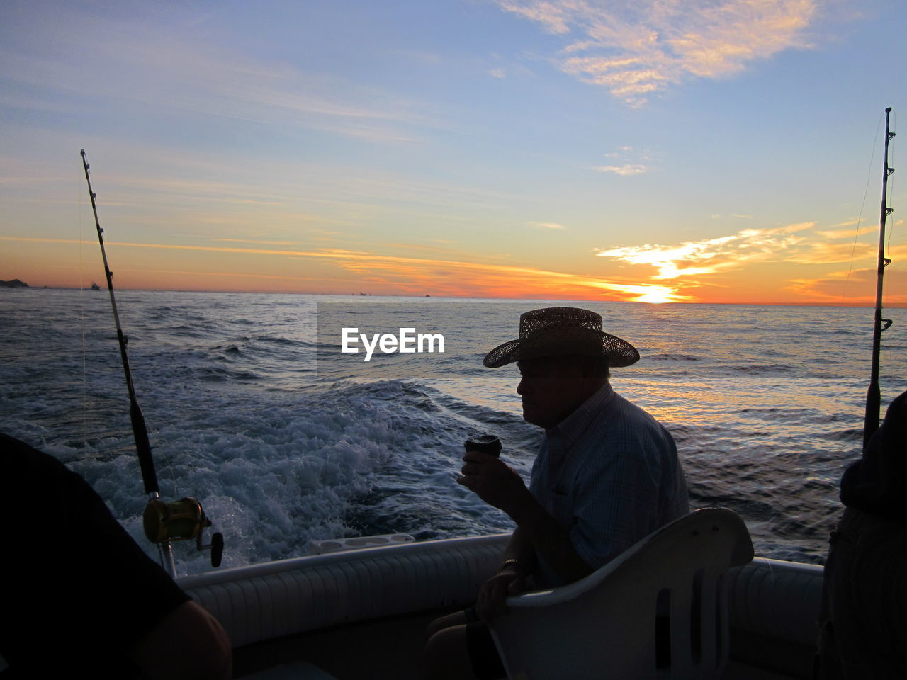 sea, sunset, real people, water, horizon over water, one person, nature, fishing, beauty in nature, fishing pole, sitting, scenics, sky, silhouette, leisure activity, men, outdoors, lifestyles, standing, wave, fishing tackle, day, people