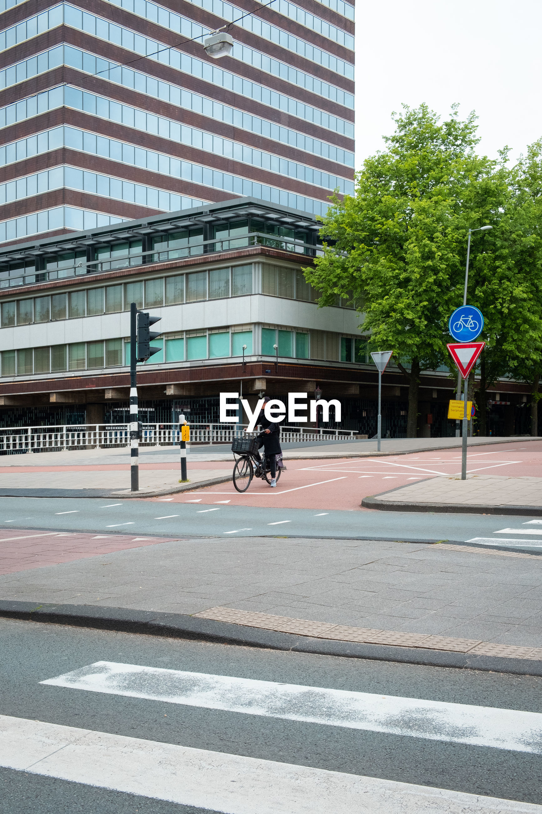 city, architecture, transportation, building exterior, road, built structure, bicycle, street, sign, land vehicle, symbol, mode of transportation, road marking, real people, riding, ride, day, men, marking, people, outdoors