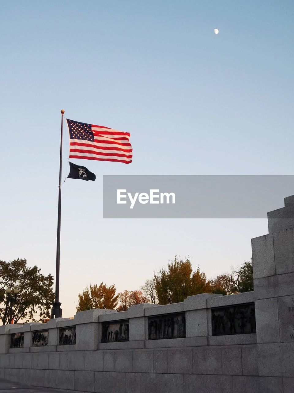 patriotism, flag, sky, architecture, low angle view, pride, clear sky, nature, built structure, no people, waving, outdoors, building exterior, day, pole, tree, emotion, independence, national icon