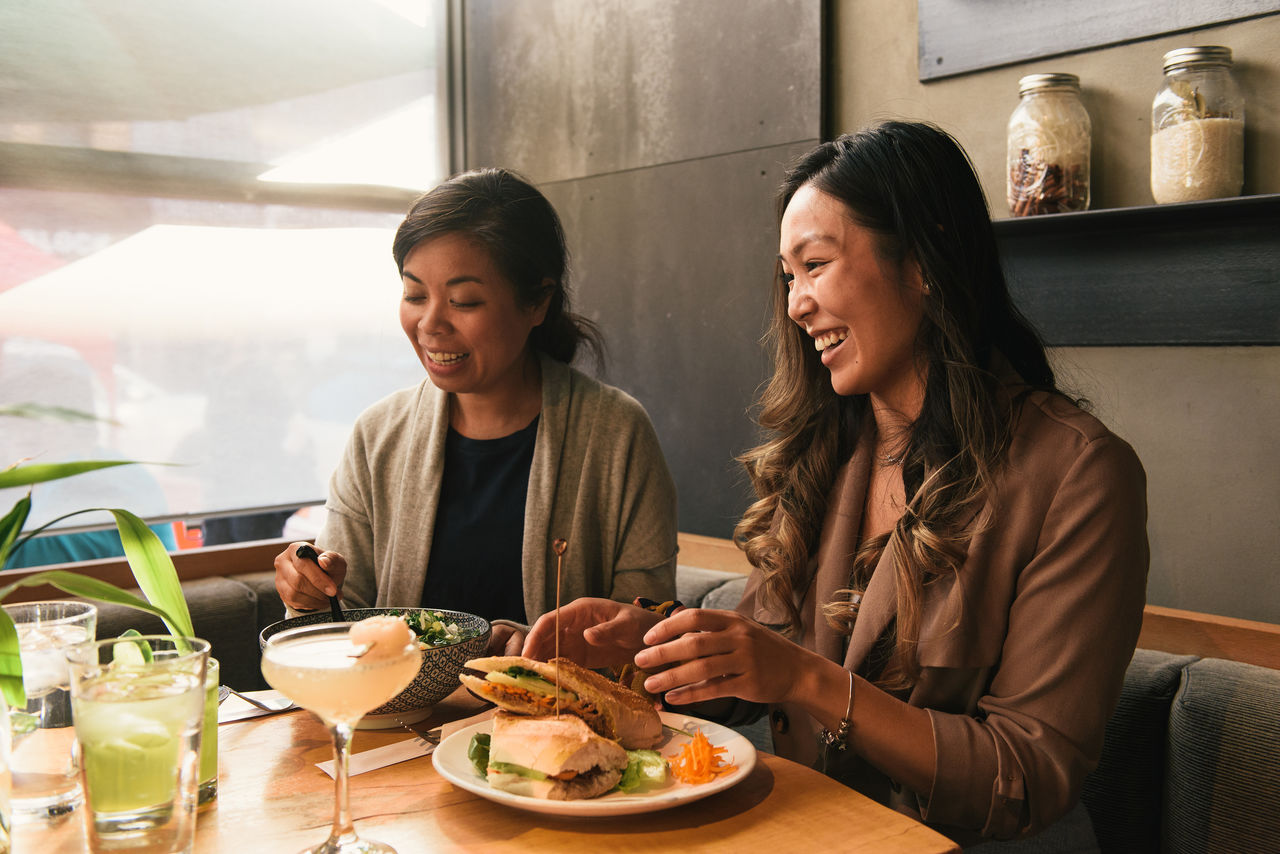 WOMAN SITTING AT RESTAURANT TABLE