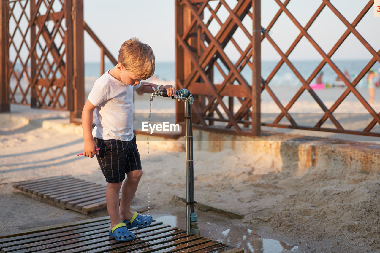 Full length of boy standing on metal structure