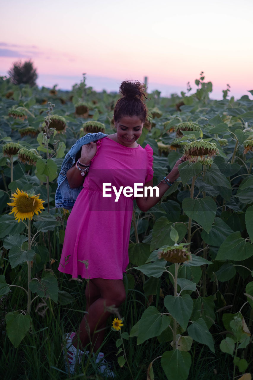 WOMAN STANDING BY PINK FLOWERS ON FIELD AGAINST SKY