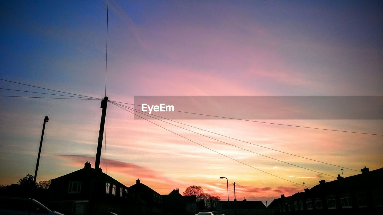 sky, architecture, sunset, building exterior, built structure, cable, building, cloud - sky, electricity, silhouette, no people, power line, nature, house, residential district, orange color, city, outdoors, connection, technology, power supply, romantic sky