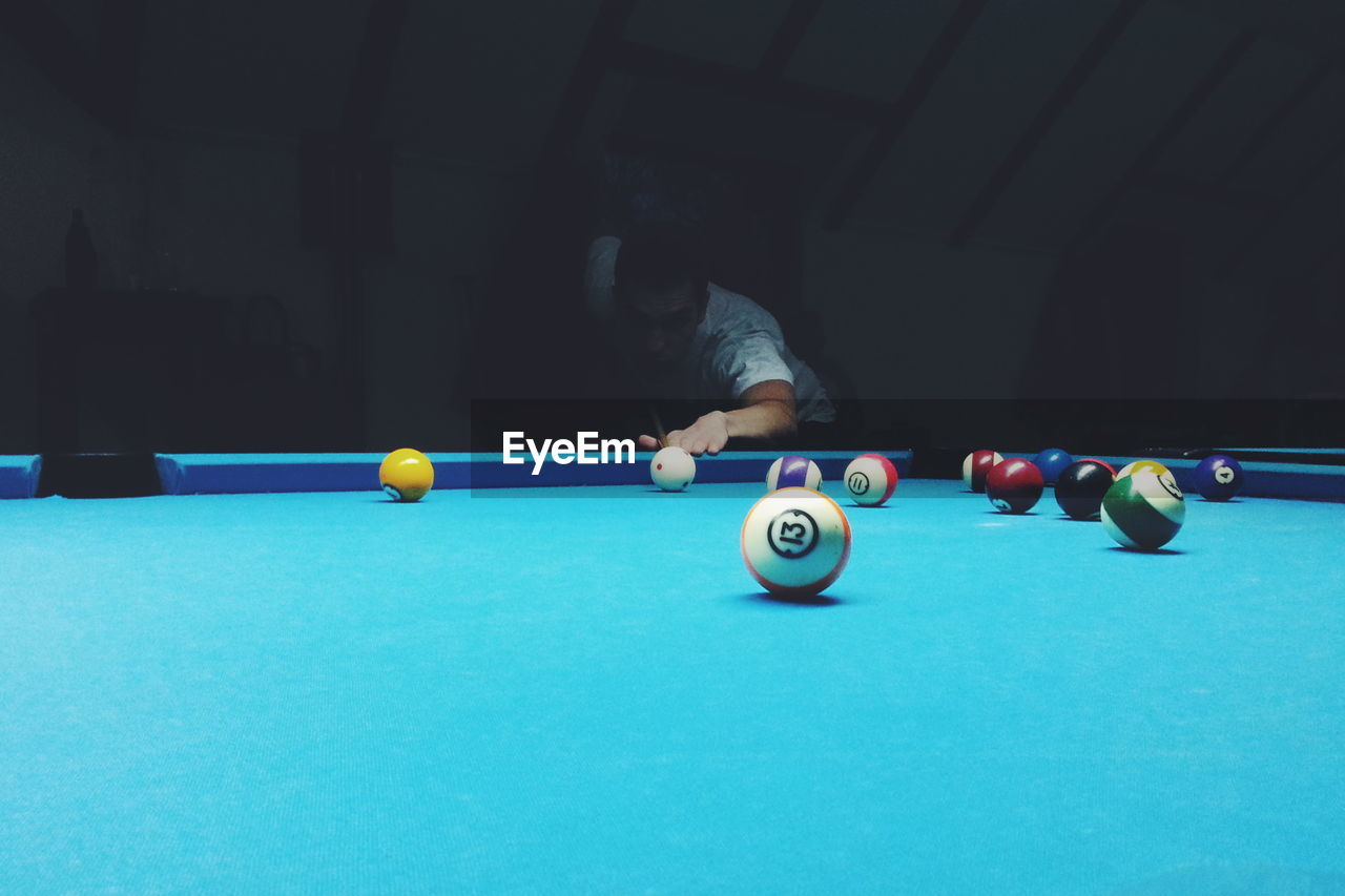 pool ball, ball, pool table, sport, table, pool - cue sport, leisure activity, one person, real people, pool cue, playing, aiming, indoors, men, lifestyles, snooker ball, accuracy, bending, skill