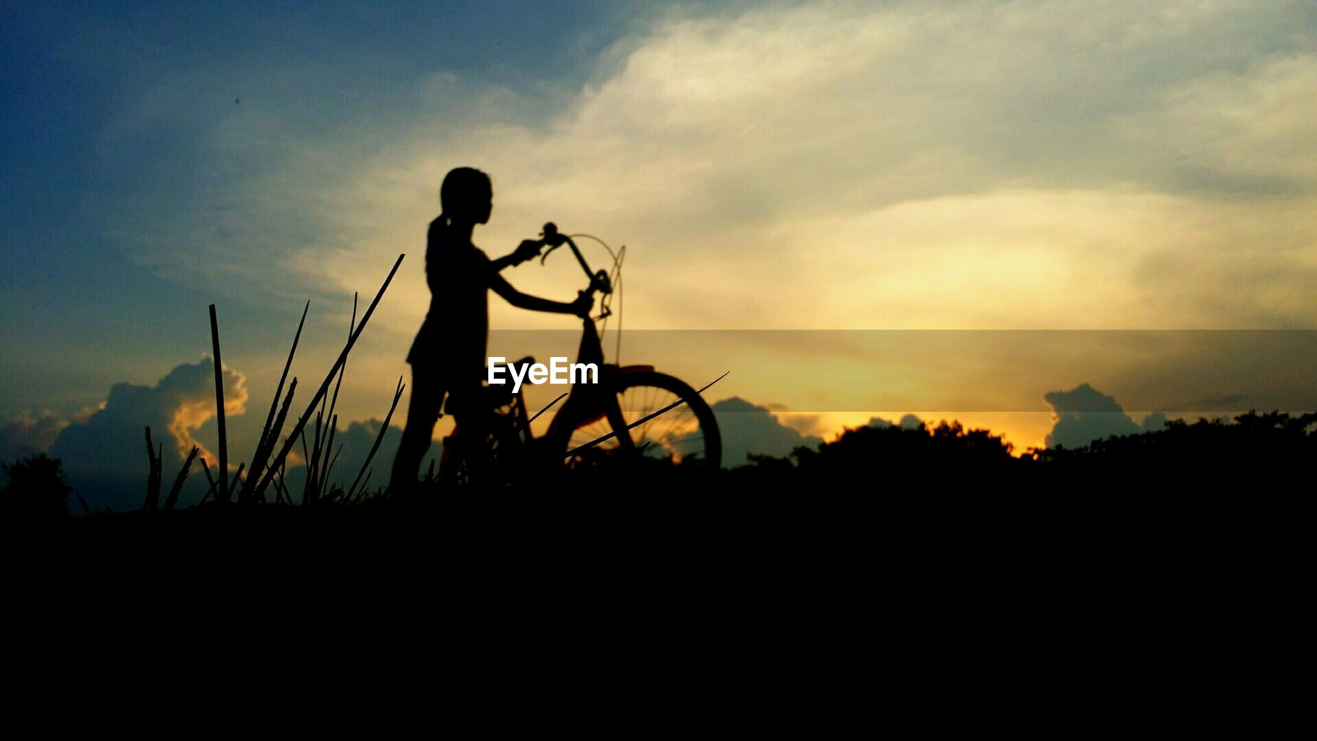 Low angle view of silhouette girl with bicycle on field against sky