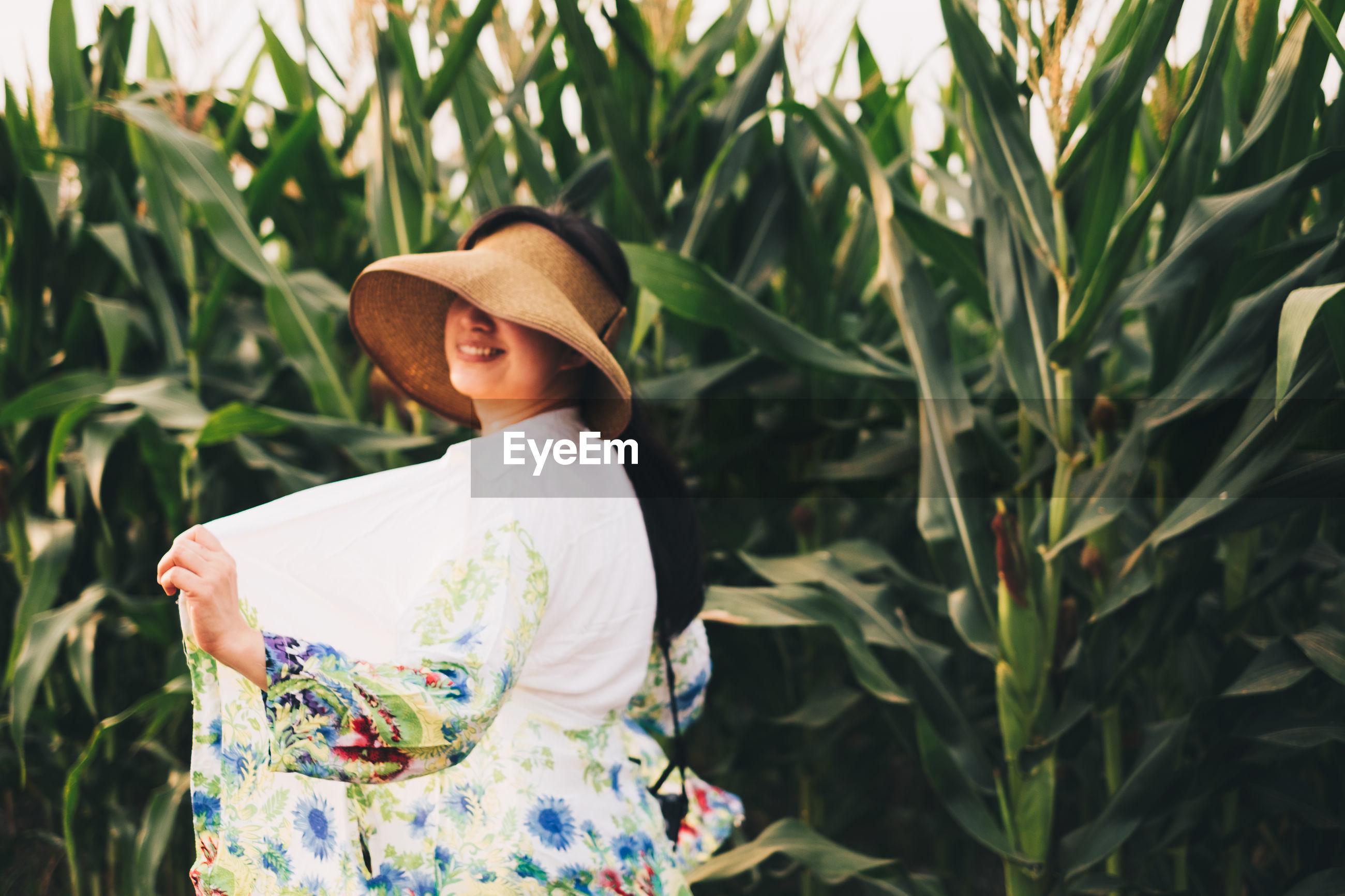 Woman standing by plants on field