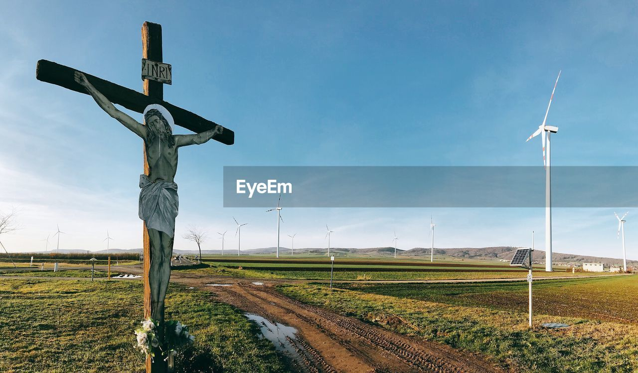 environment, field, sky, land, landscape, cross, nature, grass, religion, rural scene, day, no people, belief, fuel and power generation, spirituality, wind turbine, turbine, environmental conservation, tranquility