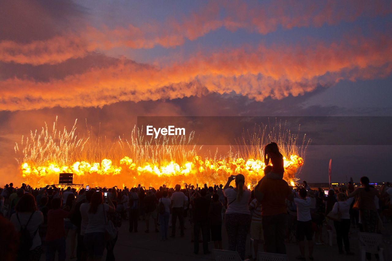 Rear view of people against firework