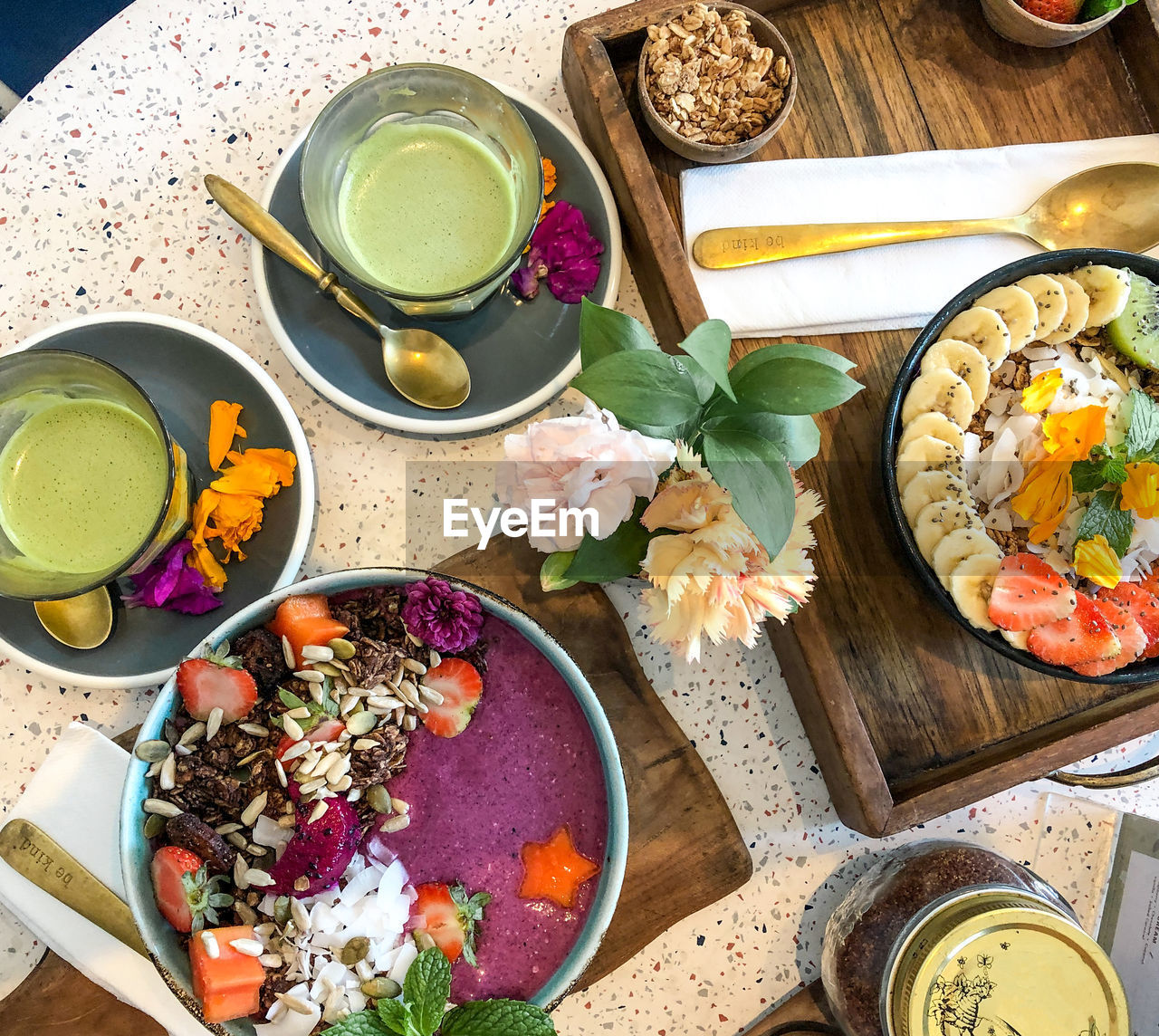 food and drink, freshness, food, table, kitchen utensil, healthy eating, high angle view, bowl, drink, wellbeing, refreshment, directly above, spoon, eating utensil, indoors, household equipment, flower, ready-to-eat, still life, flowering plant, no people, meal, glass, breakfast, crockery