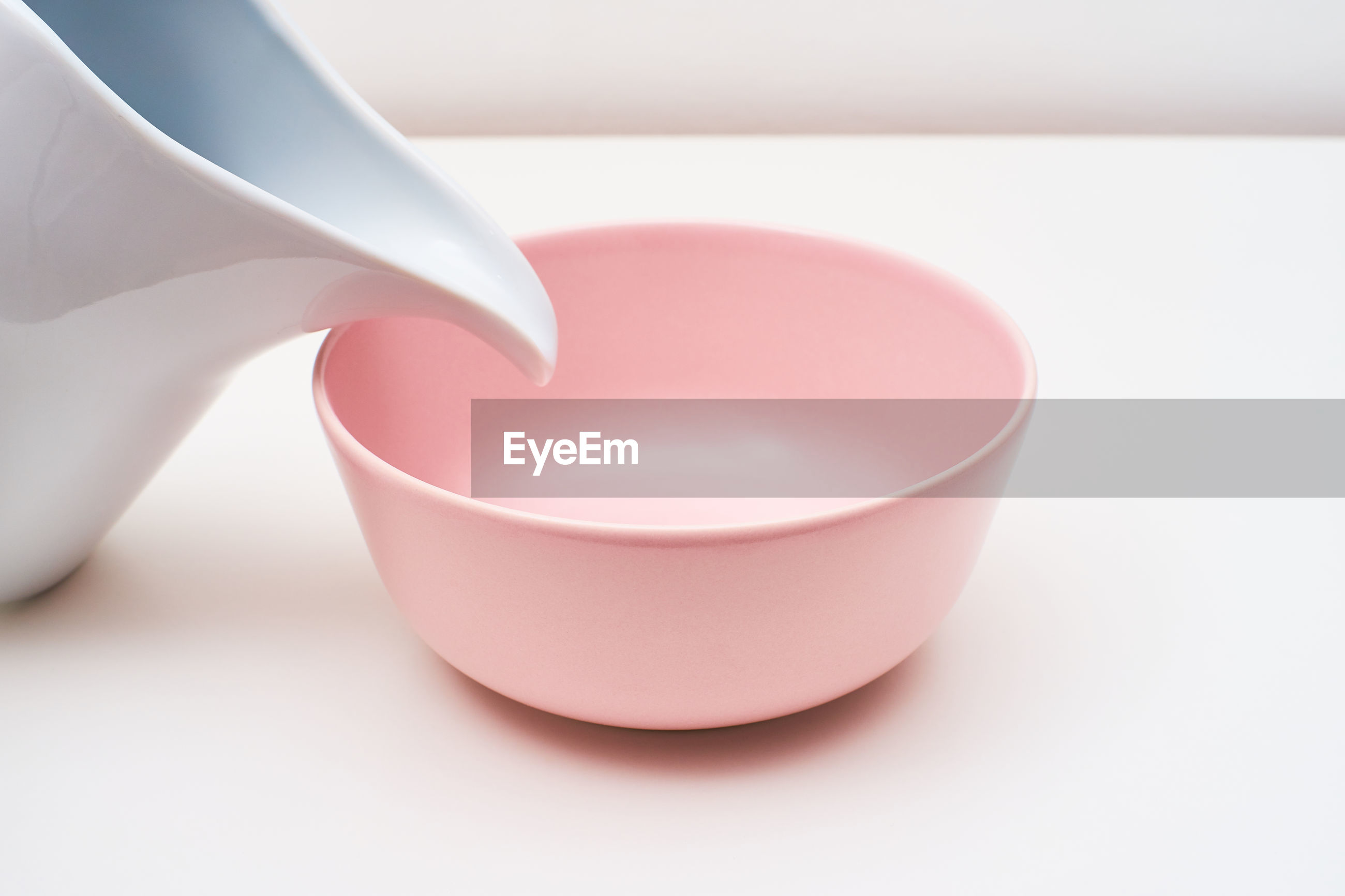 A pink bowl and a white carafe on a table