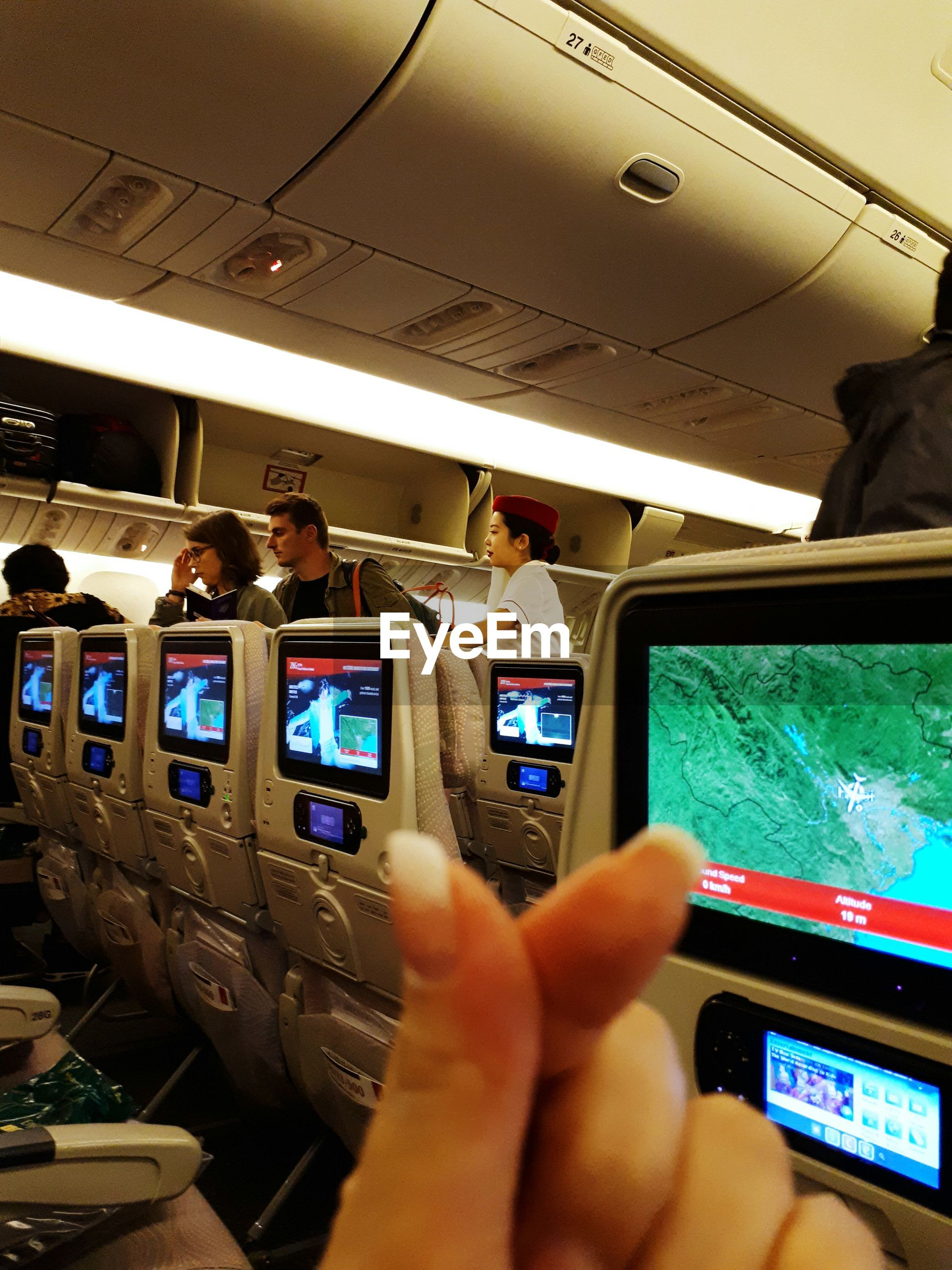 vehicle interior, technology, transportation, real people, device screen, mode of transport, computer, wireless technology, human hand, airplane, air vehicle, liquid-crystal display, illuminated, indoors, day, one person, people
