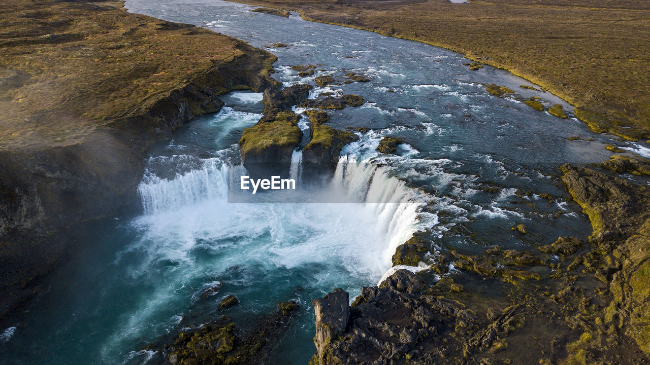 HIGH ANGLE VIEW OF WATERFALL BY SEA