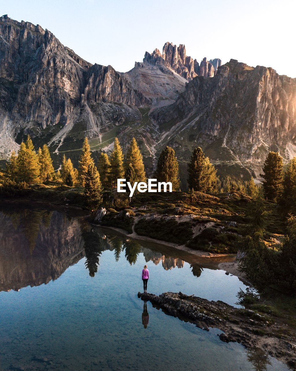REFLECTION OF MAN IN LAKE AGAINST MOUNTAIN