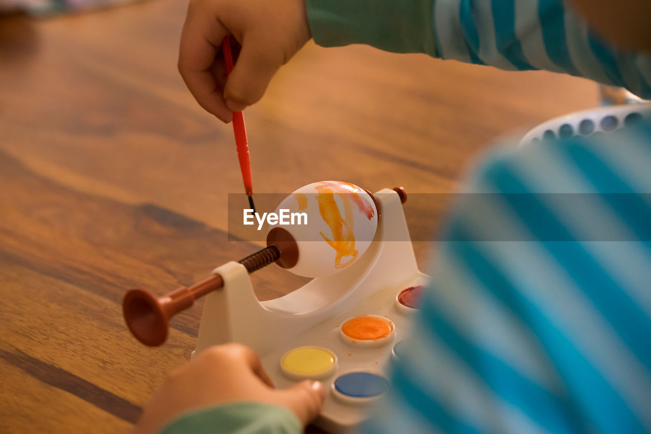 Midsection Of Boy Painting Egg During Easter