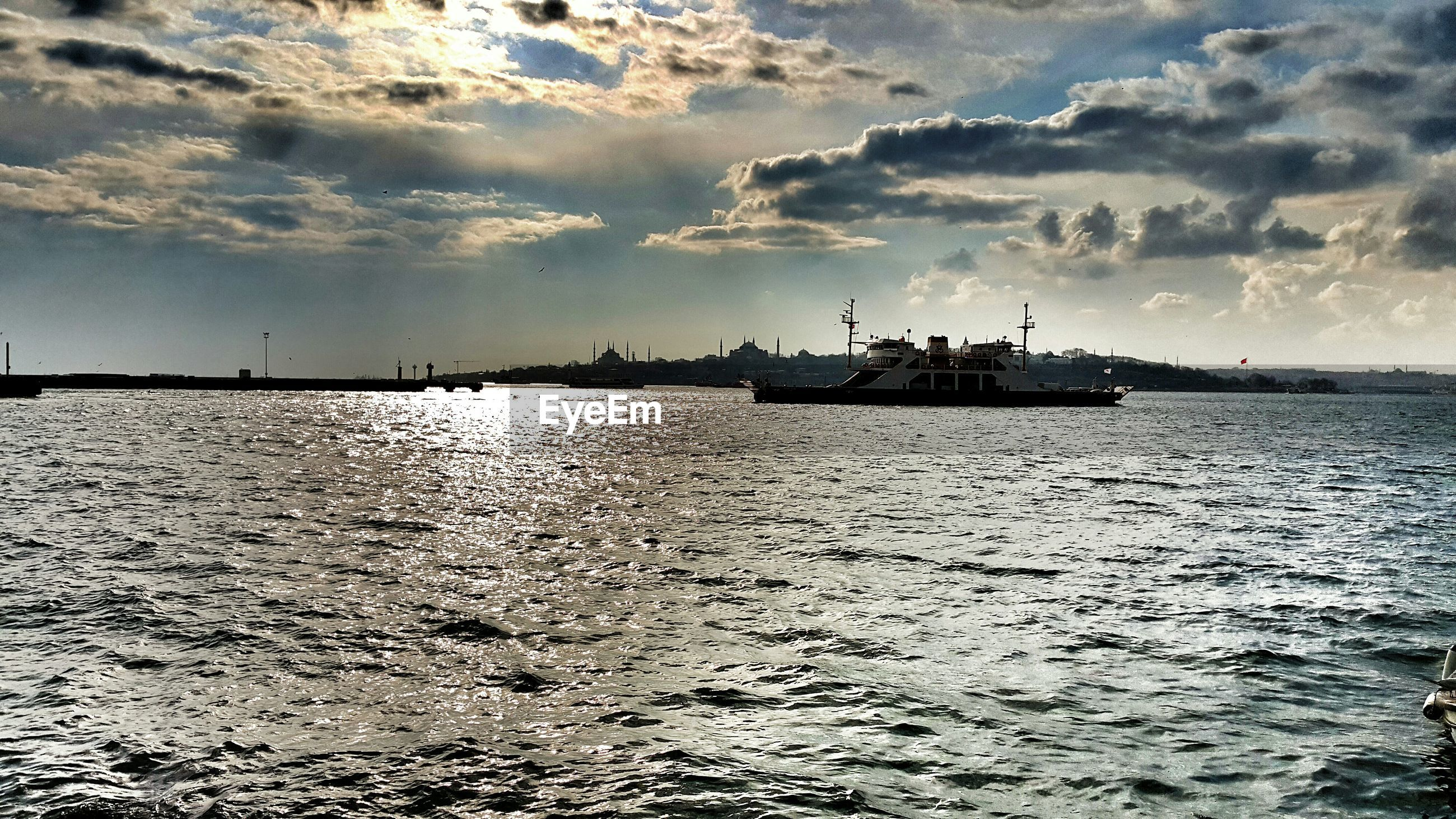water, sea, waterfront, sky, rippled, tranquility, transportation, tranquil scene, cloud - sky, nautical vessel, scenics, nature, beauty in nature, mode of transport, cloud, boat, cloudy, outdoors, silhouette, built structure