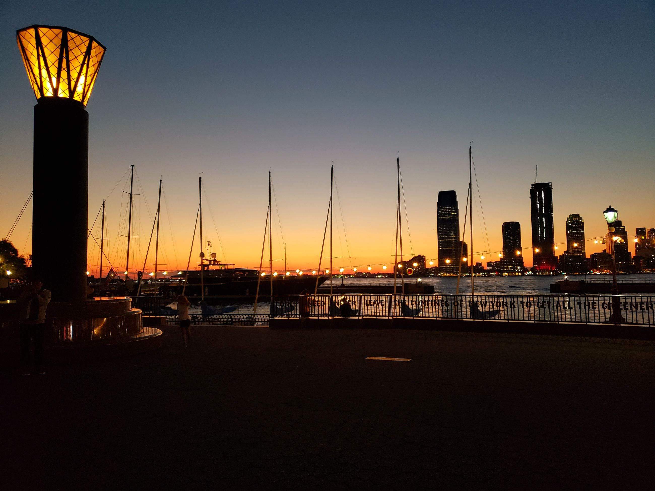 SAILBOATS IN CITY AT SUNSET