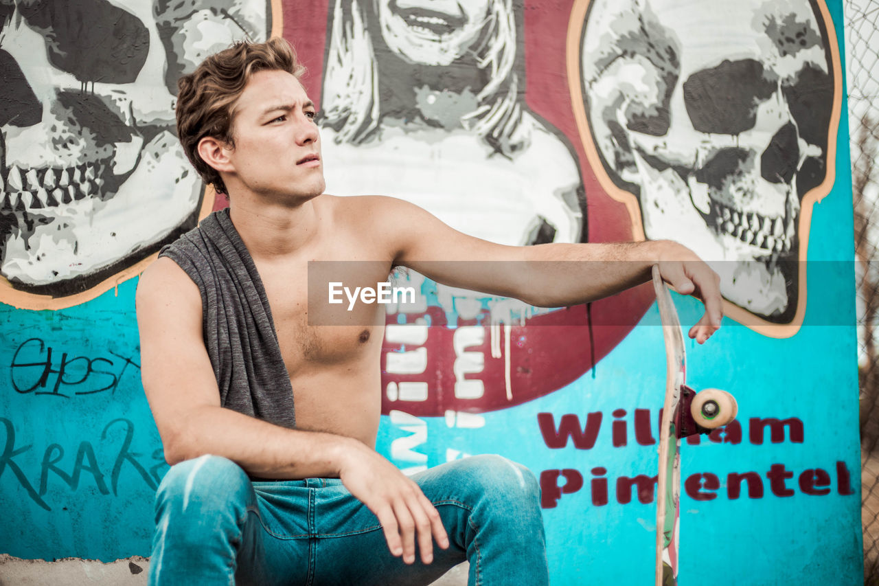 graffiti, young men, young adult, three quarter length, one person, front view, art and craft, lifestyles, shirtless, casual clothing, creativity, real people, text, men, street art, leisure activity, paint, holding, jeans, chest, shorts