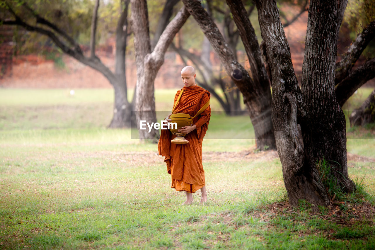 Full length of monk wearing traditional clothing standing in forest
