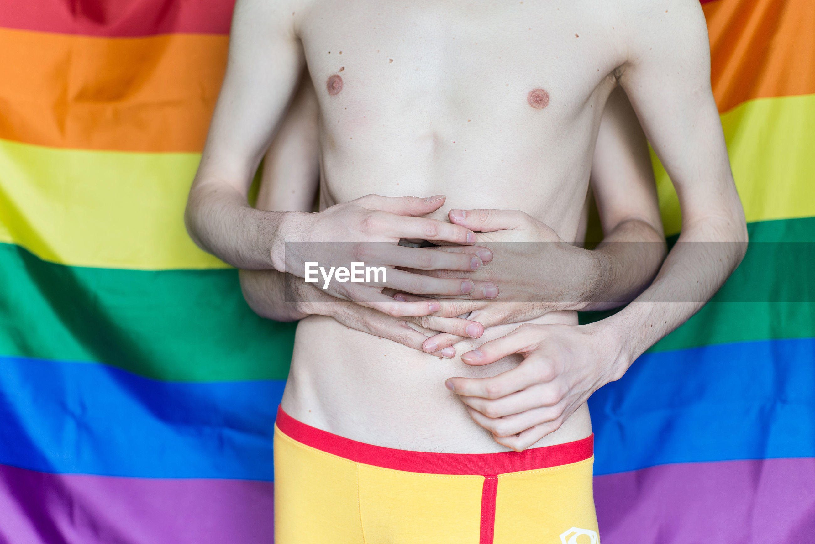 Midsection of gay couple embracing while standing against rainbow flag
