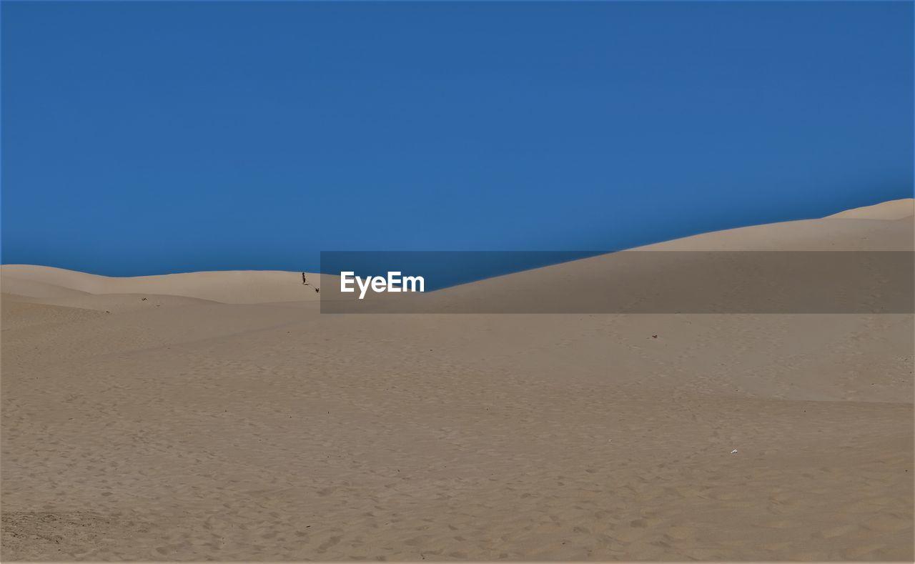 SAND DUNES AGAINST CLEAR BLUE SKY