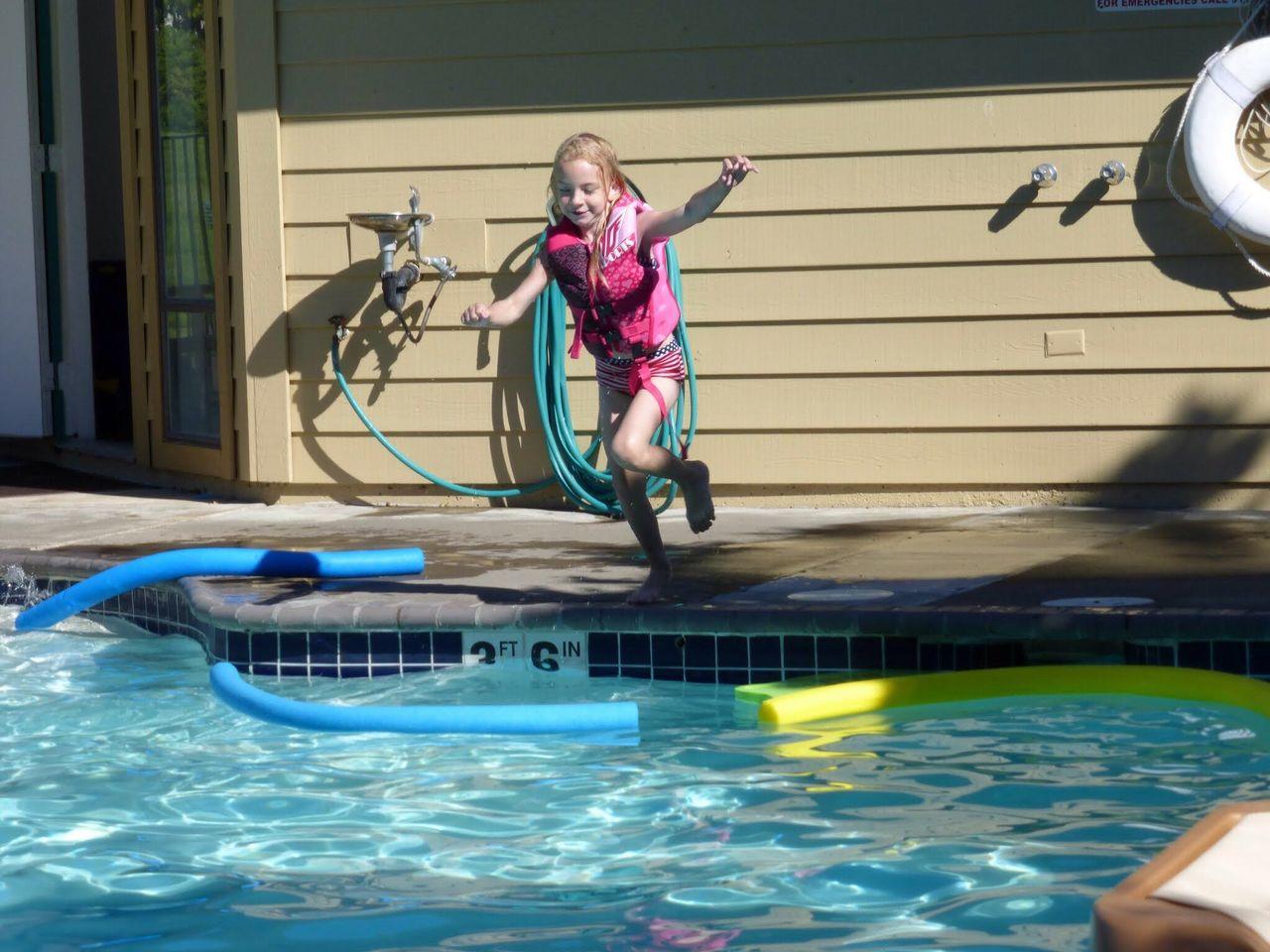 Full length of girl diving into swimming pool