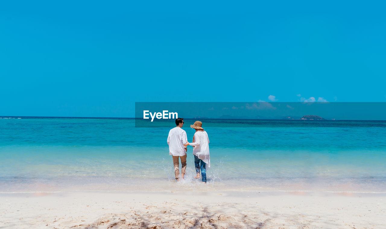 Rear view of couple walking in sea