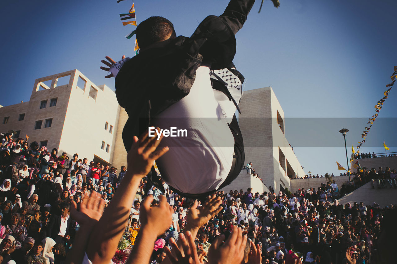 Crowd Throwing Man Mid-Air During Graduation Ceremony