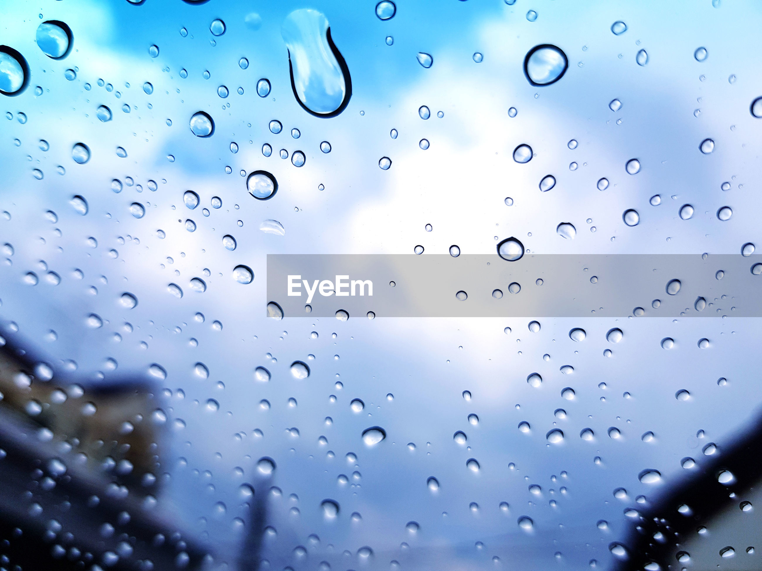 CLOSE-UP OF RAINDROPS ON WINDOW GLASS