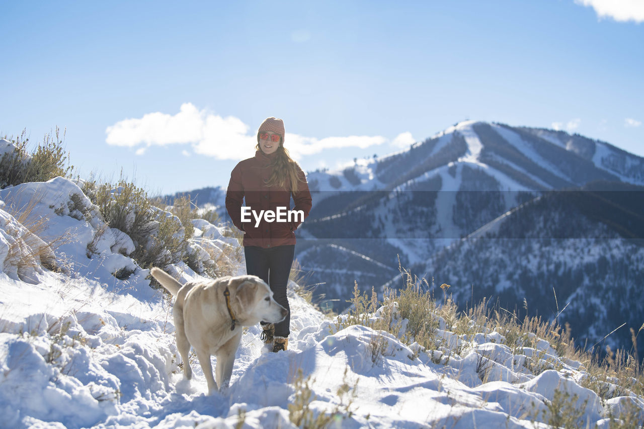 DOG STANDING ON SNOW COVERED MOUNTAINS