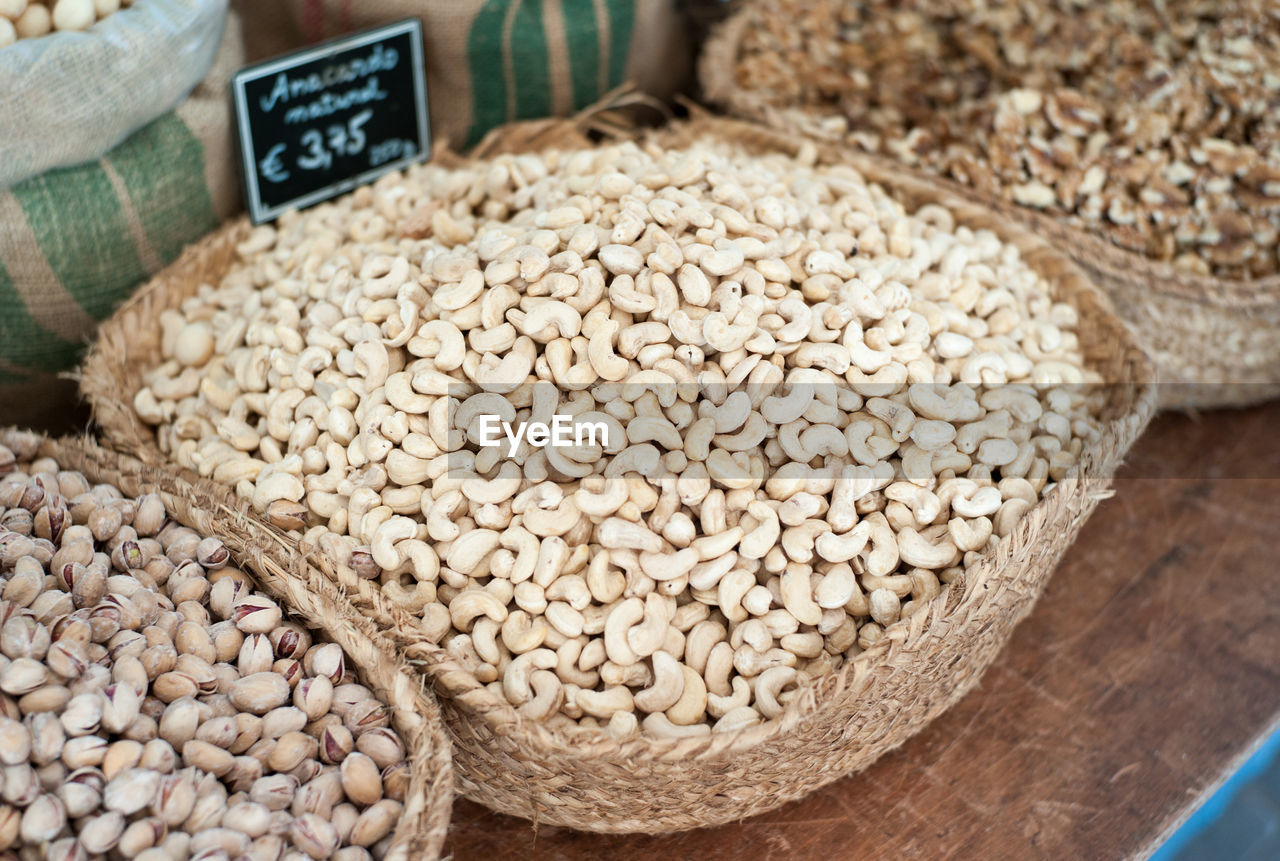 High angle view of cashew nuts in basket at market for sale