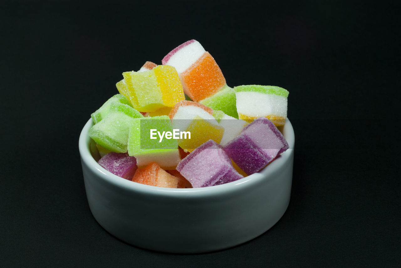 Close-Up Of Candies In Bowls Against Black Background