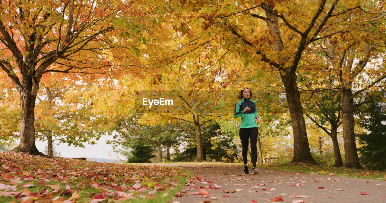 Young Woman On Running Amidst Autumn Trees