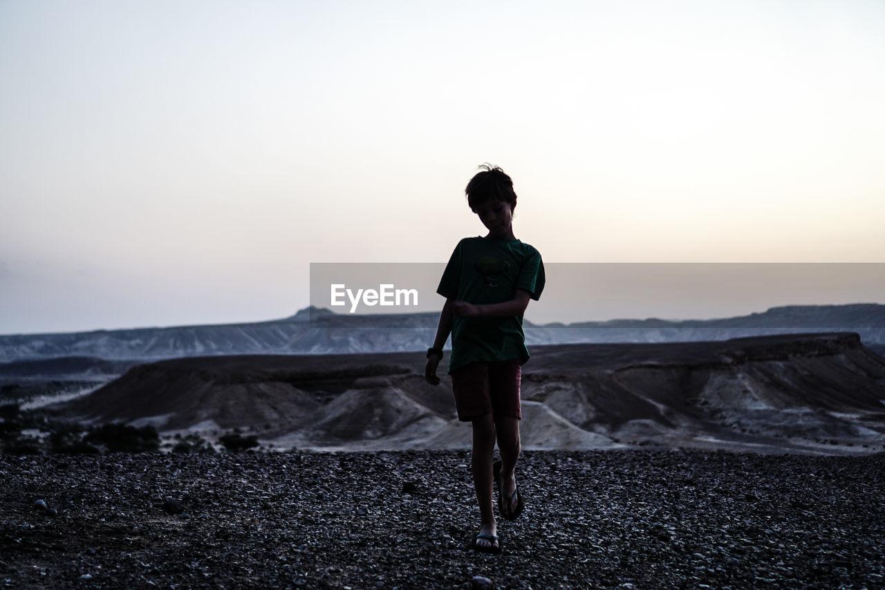 Full length of child standing on land against sky during sunset