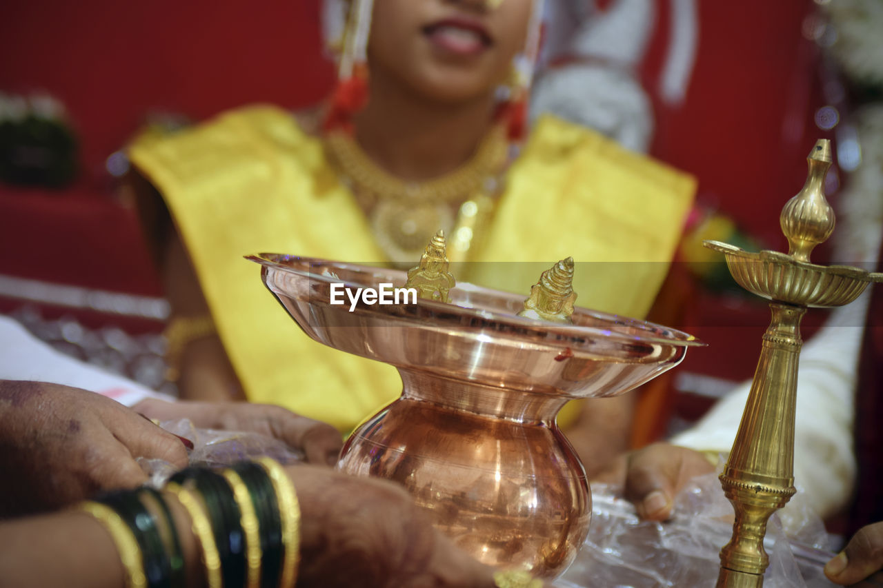 Midsection of couple holding utensils at wedding ceremony