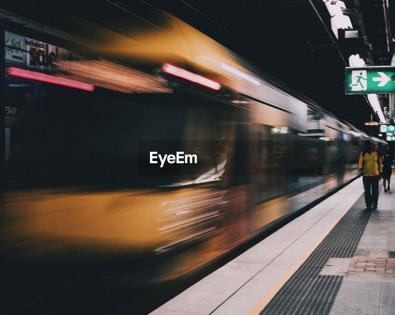 Blurred Motion Of Train By People Walking At Railroad Station Platform
