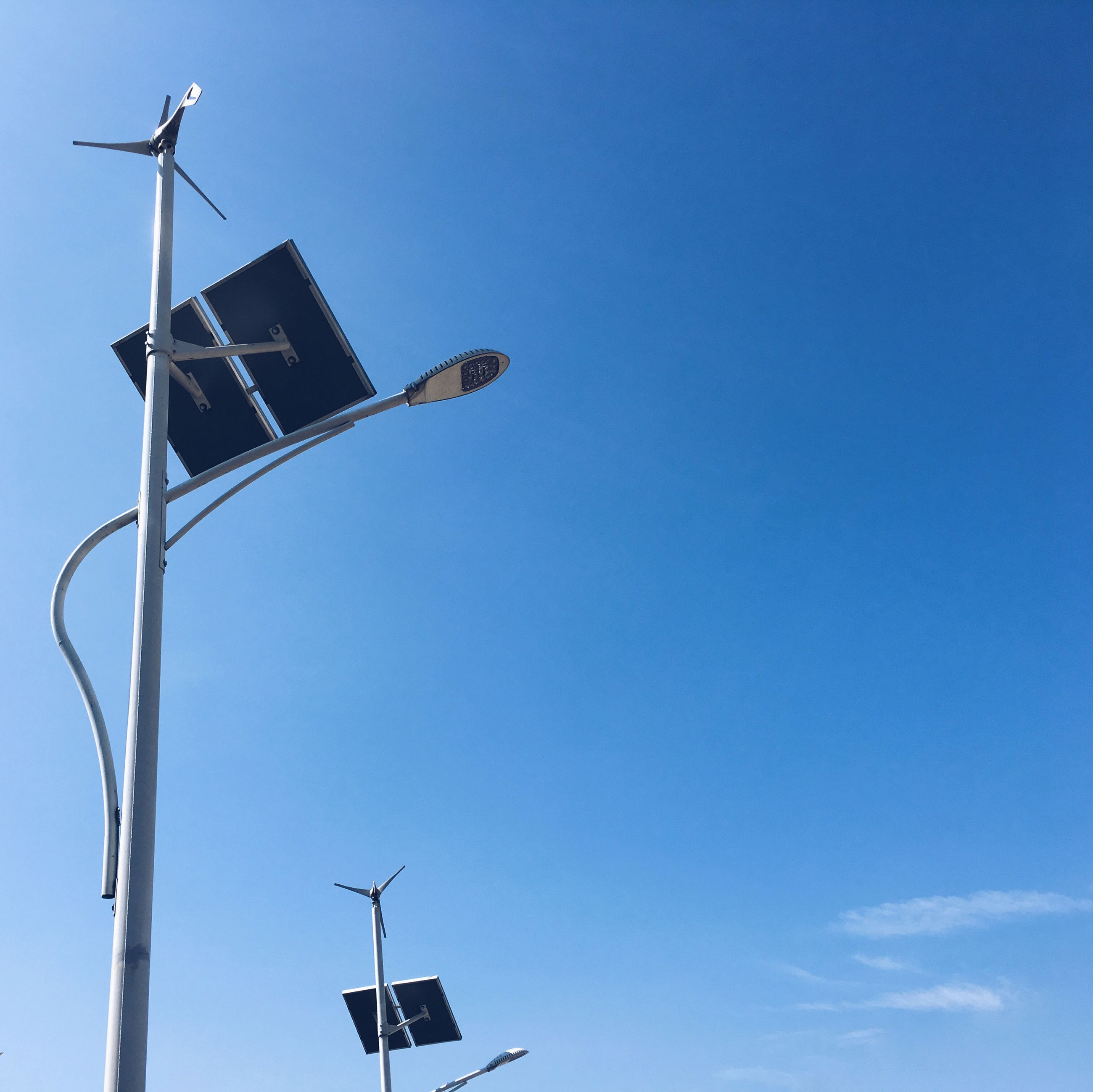 Low angle view of street light by wind turbine against blue sky