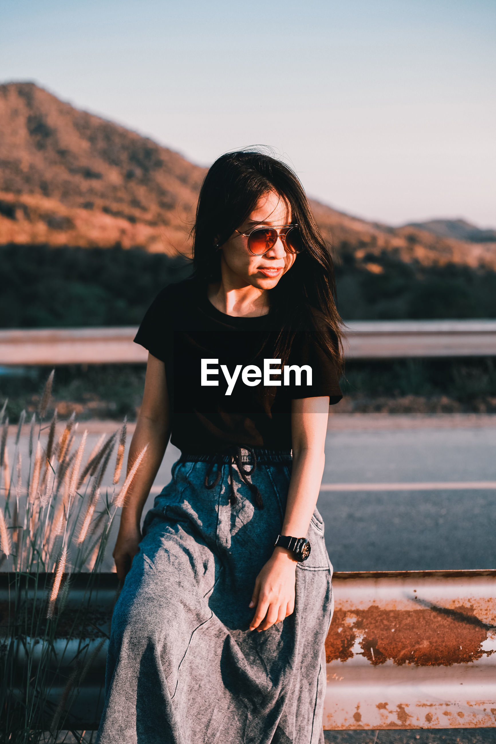 BEAUTIFUL YOUNG WOMAN WEARING SUNGLASSES ON RAILING AGAINST SKY
