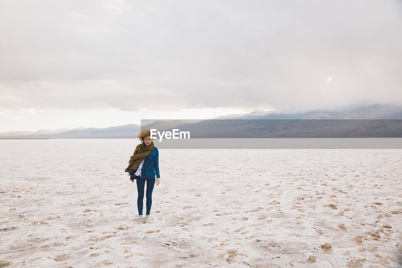 Young Woman Standing At Death Valley National Park Against Cloudy Sky