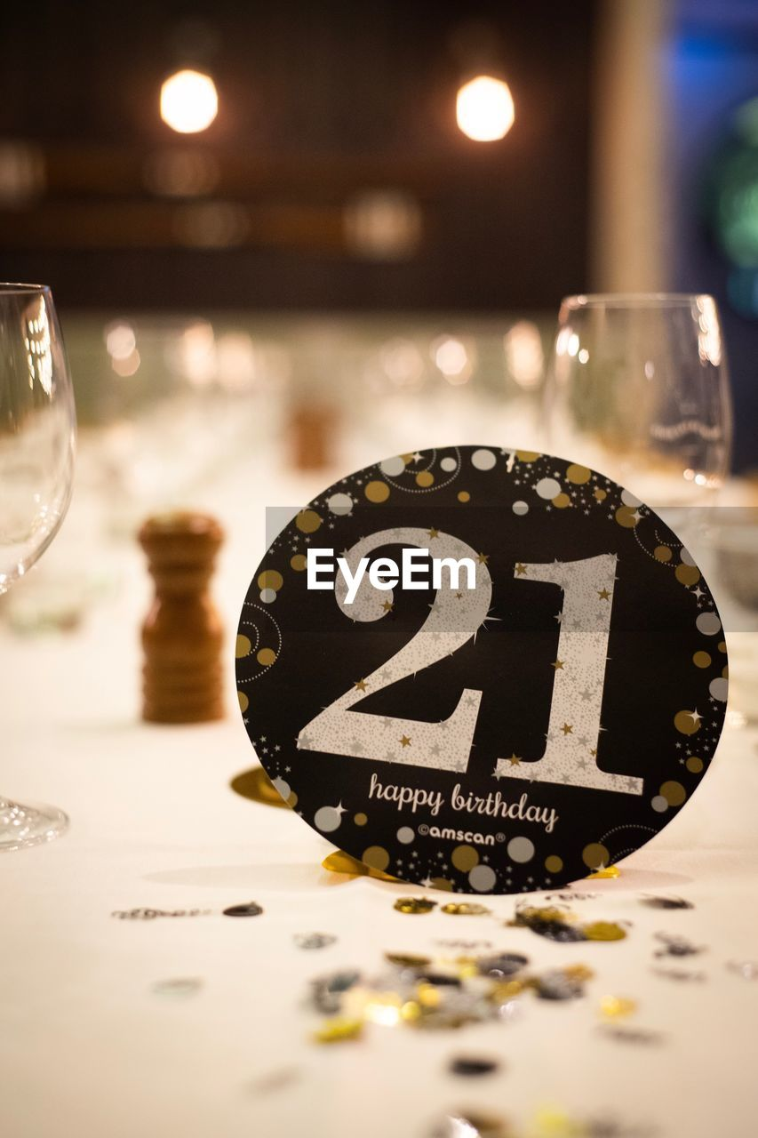 number, illuminated, communication, close-up, no people, text, table, selective focus, indoors, night, western script, still life, sign, focus on foreground, reflection, business, lighting equipment, information, glass - material, food and drink