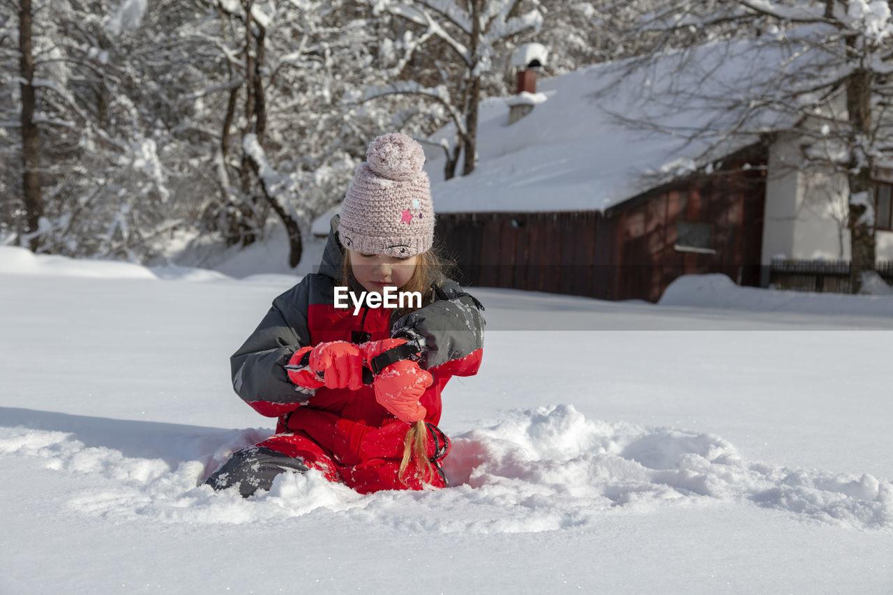 Young girl is having winter fun on a snowy, sunny day in lika, croatia