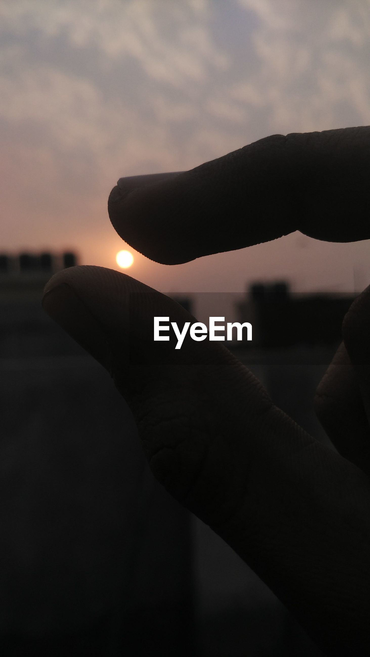 person, part of, sky, human finger, holding, cropped, focus on foreground, unrecognizable person, lifestyles, close-up, personal perspective, leisure activity, silhouette, sunset, men, sunlight