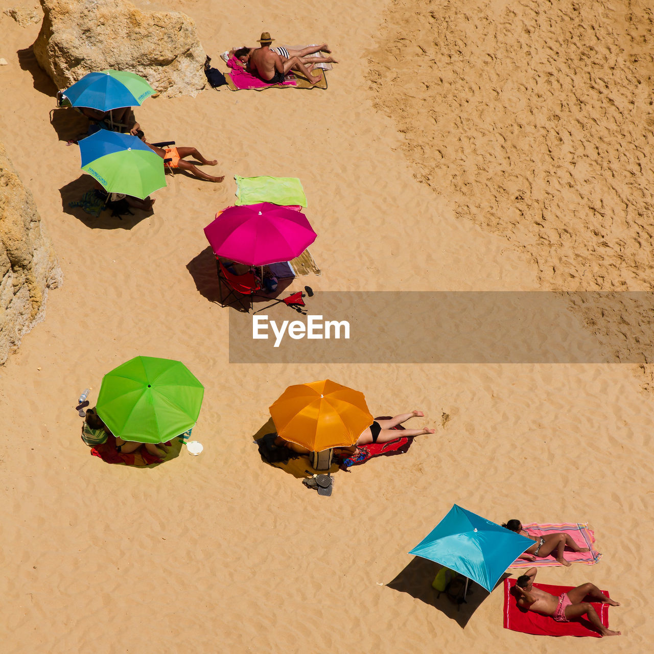 High angle view of multi colored parasols on sand