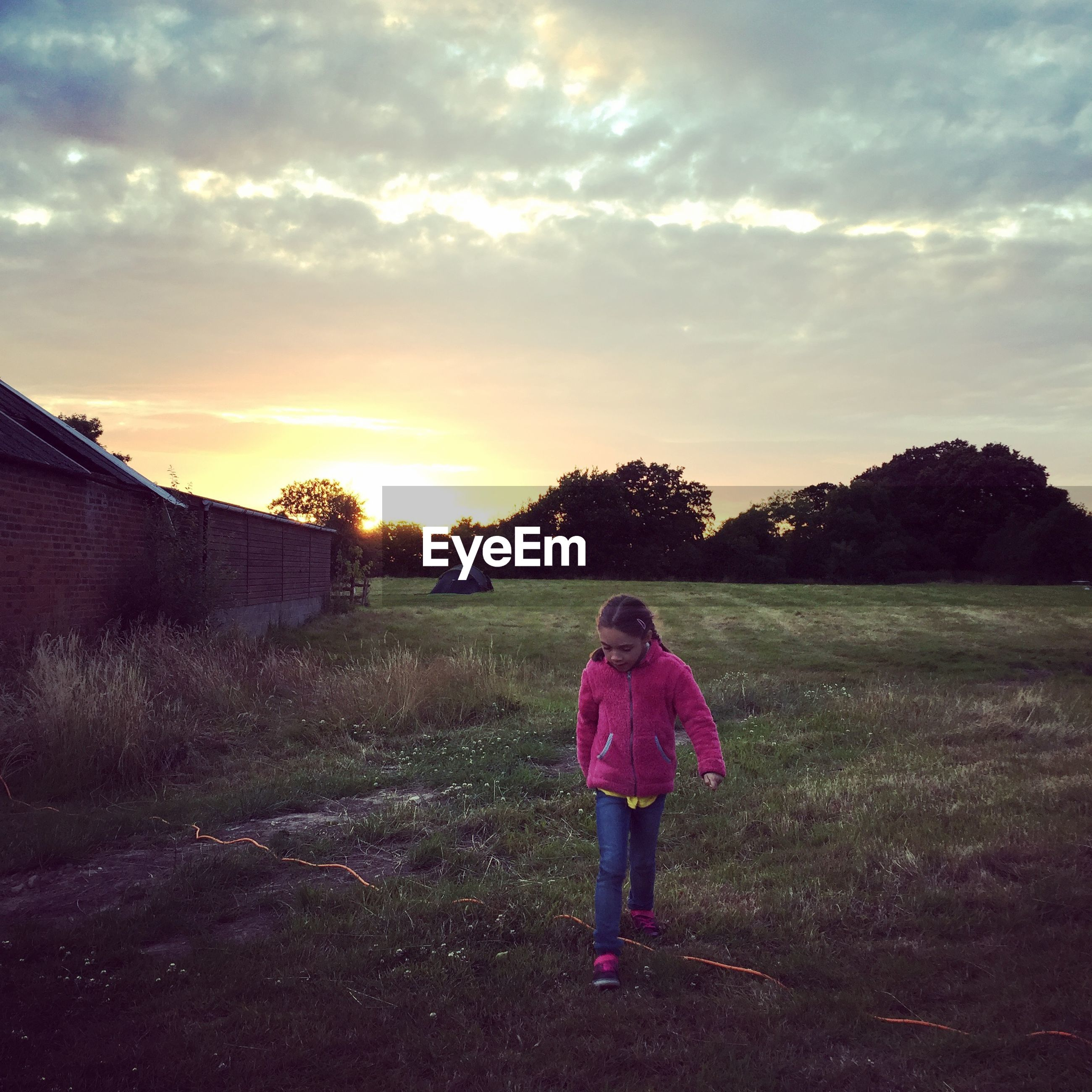 Girl walking on grassy field against cloudy sky during sunset
