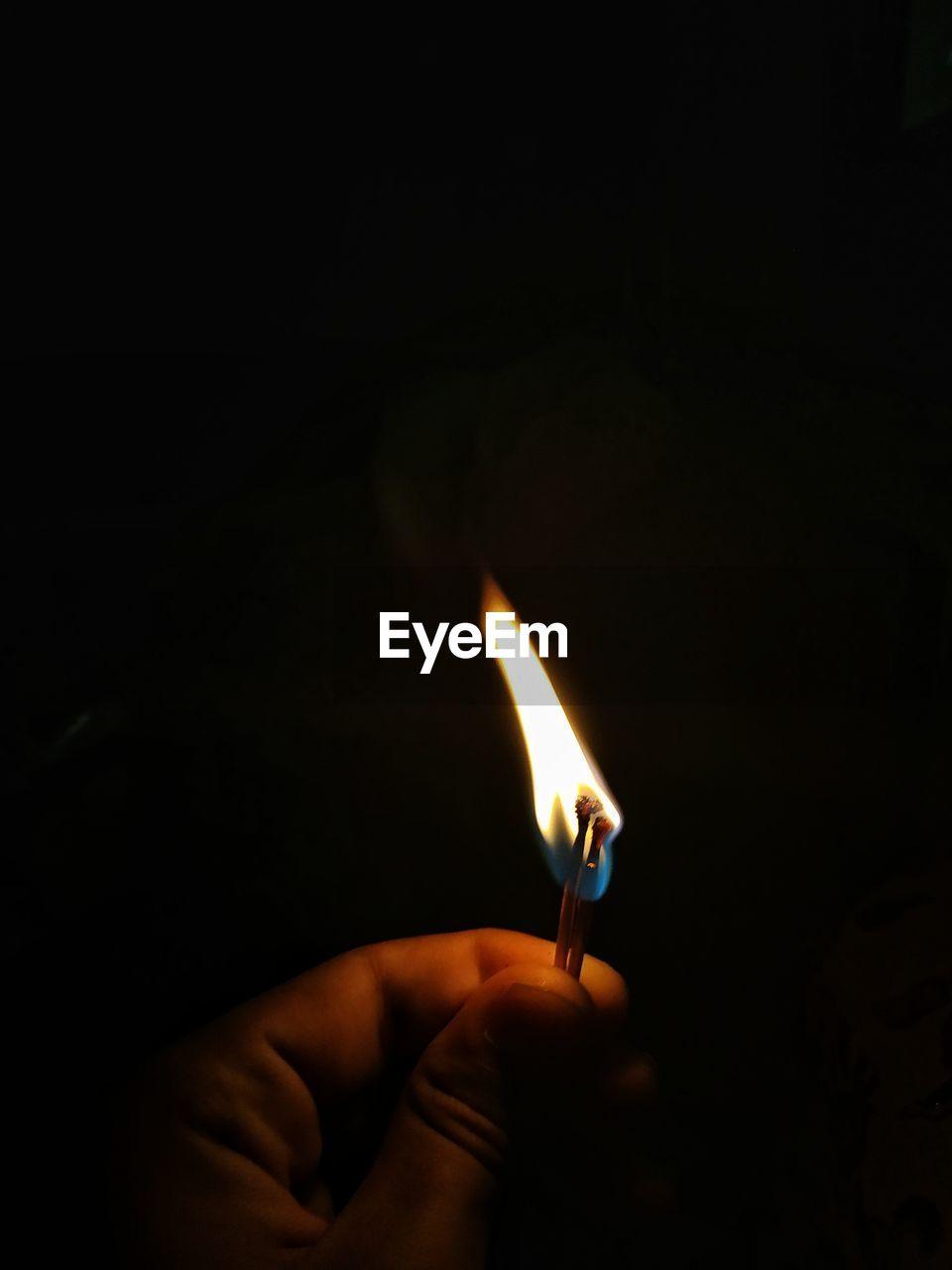Close-up of hand holding burning matchstick over black background