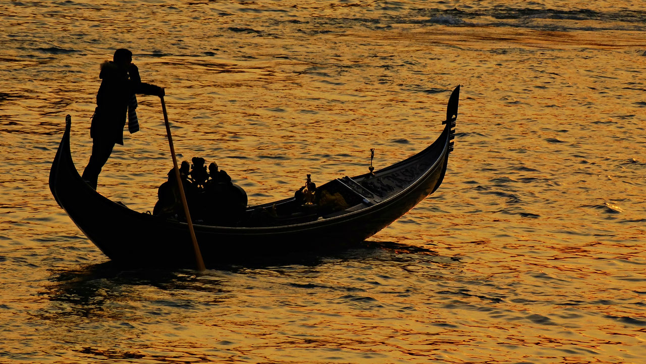 Silhouette Gondolier On Gondola In Grand Canal During Sunset